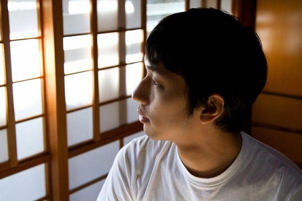 光がさす部屋で我慢していることを考えている男性の写真