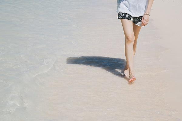 海辺を素足で歩いている健康的な女性の写真