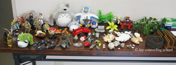 箱庭療法の人形がテーブルに並べられている写真