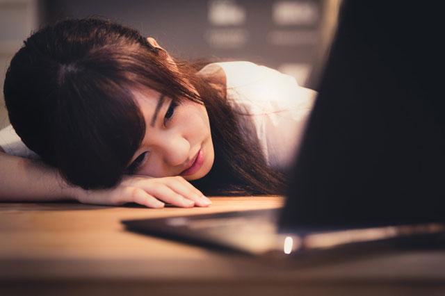 笑顔を心がけ過ぎて疲れて横たわる女性