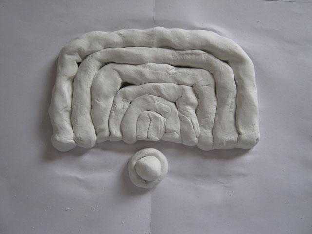 小さな造形を円状の粘土で包み込む